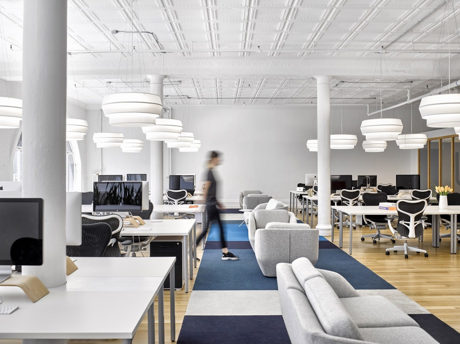 Modern open concept office space with couches, workstations, and chandelier lighting
