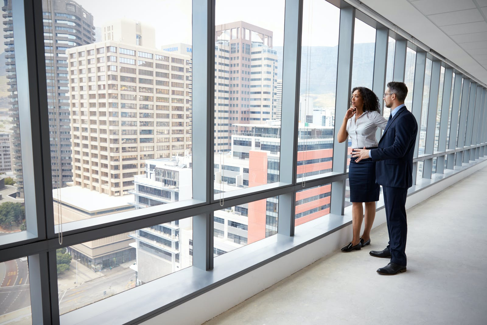 business partners looking out window at skyline - Truss