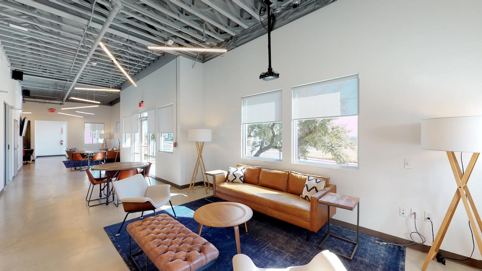 Comfortable and stylish open coworking space with leather couches and benches, cozy chairs, and modern lighting fixtures