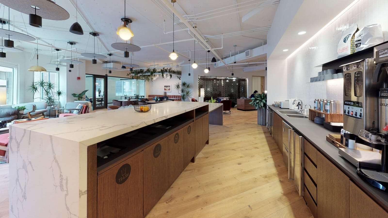 Cafe area and open seating in a large modern coworking space with many amenities
