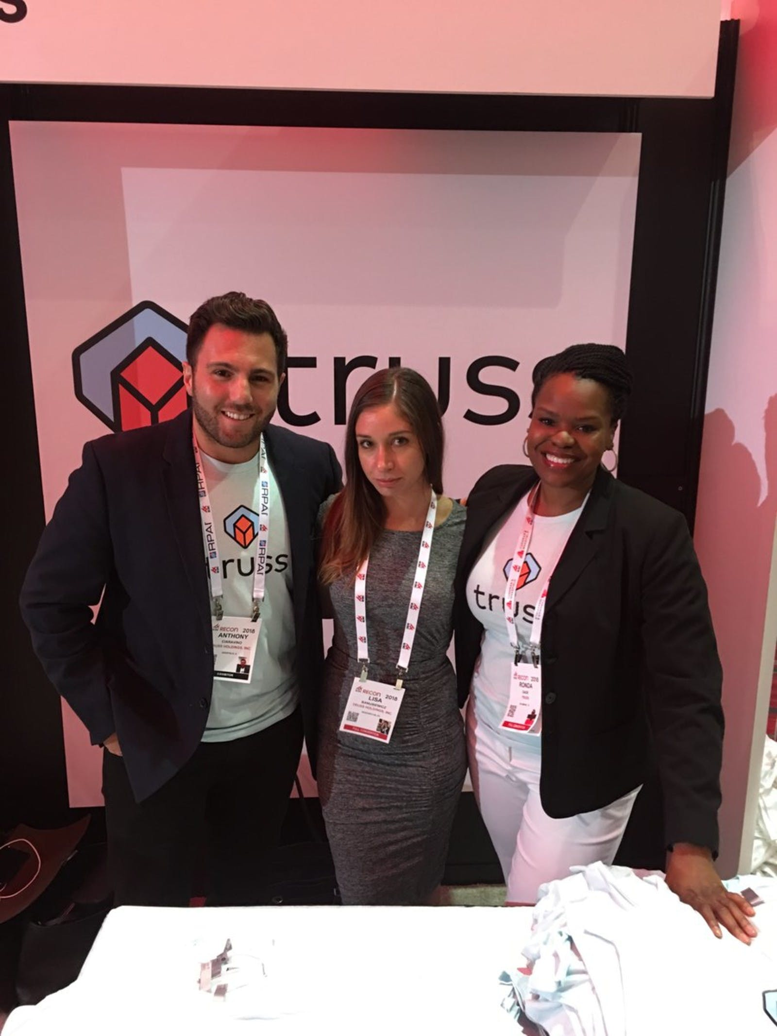 Truss team members at ICSCRECon in Las Vegas standing in front of a Truss logo banner